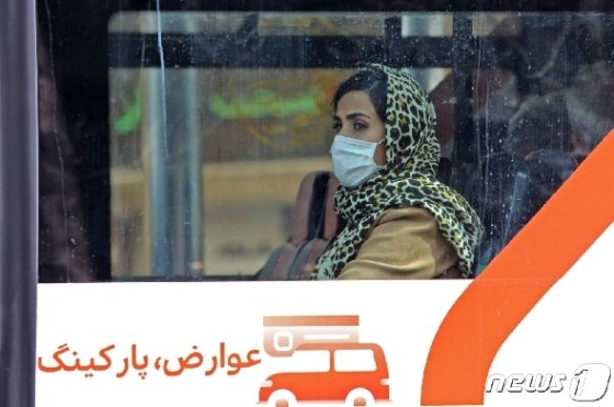 24일 이란 수도 테헤란에서 한 버스를 탄 여성이 마스크를 착용하고 있다. © AFP=뉴스1