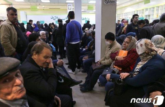 지난 19일 이란 수도 테헤란의 한 약국에서 시민들이 약 처방을 받기 위해 대기 중이다. © AFP=뉴스1