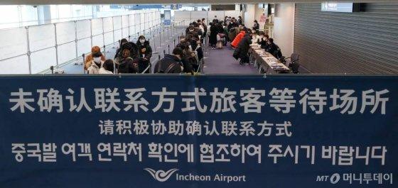 인천국제공항 제1터미널 중국발 항공기 전용 입국장에서 탑승객들이 국내 연락 가능한 연락처를 확인받고 있다. / 사진=이기범 기자 leekb@