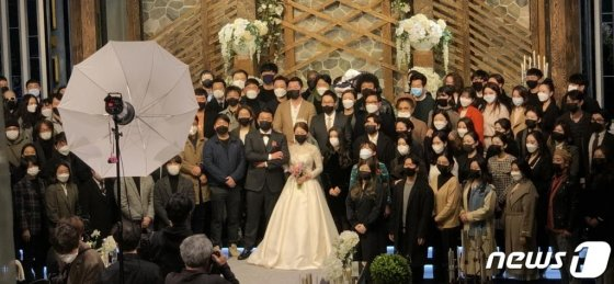(서울=뉴스1) = 22일 오후 서울 마포구 한 예식장에서 마스크를 쓴 신랑 신부와 하객들이 기념사진을 찍고 있다. 이 사진은 신종 코로나바이러스 감염증의 위험성과 마스크 착용의 필요성을 알리기 위한 결혼식 주최측의 제안과 참석자들의 동의 아래 촬영됐다. (독자 제공) 2020.2.22/뉴스1  <저작권자 © 뉴스1코리아, 무단전재 및 재배포 금지>