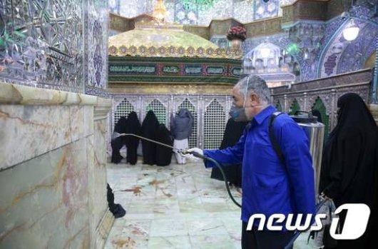 이란 곰(Qom) 지역에서 한 직원이 사원을 소독하고 있다./사진=AFP
