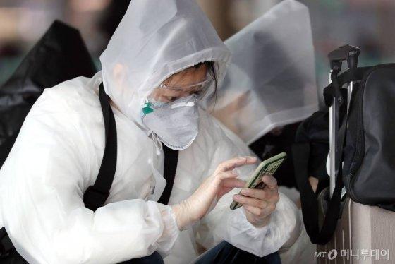 코로나19 국내 확산이 빠르게 진행되고 있는 가운데 26일 인천국제공항 제1터미널 출국장에서 보호 장비를 착용한 중국인들이 휴대전화를 만지고 있다. / 사진=이기범 기자 leekb@