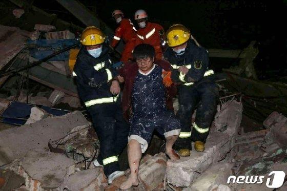 한 매몰자가 소방대원들의 도움을 받아 현장을 탈출하고 있다. © AFP=뉴스1 © News1 박형기 기자