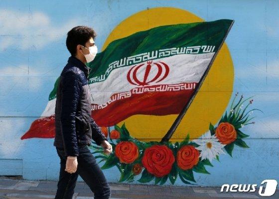 지난 4일(현지시간) 이란 수도 테헤란에서 한 남성이 이란 국기가 그려진 벽화 앞을 지나고 있다. © AFP=뉴스1