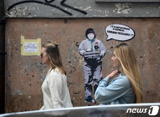"""4일(현지시간) 이탈리아 로마 중국인 구역 골목 벽면에 """"무지 속에 확산되는 전염병, 우리는 스스로 보호해야 해!""""라는 문구가 적혀 있다. © AFP=뉴스1 © News1 정윤미 기자"""