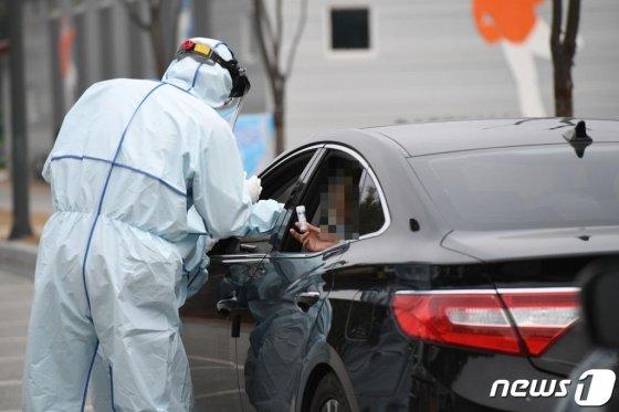 보건당국 관계자들이 검체를 채취하고 있다.(기사내용 과는 관계 없음) 검사를 받을 때는 '드라이브 쓰루' 형태가 아니더라도 감염자와의 접촉을 피하기 위해 차량을 이용하는 것이 좋다. /사진=뉴스1
