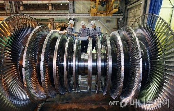 경남 창원에 위치한 두산중공업 터빈공장에서 엔지니어들이 각종 발전기에 탑재되는 터빈 로터를 검사하고 있다./사진=두산중공업