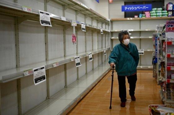일본 도쿄의 한 상점에서 한 여성이 텅빈 화장지 진열대를 지나가고 있다./사진=AFP