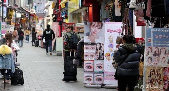 코로나19 확산이 지속되고 있는 2월 26일 오후 서울 중구 명동의 한 잡화매장 상인이 썰렁한 거리를 바라보고 있다. /사진=김창현 기자 chmt@