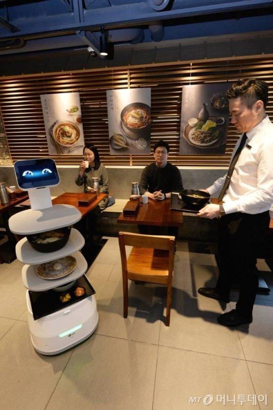 LG전자와 CJ푸드빌이 지난1월 31일 제일제면소 서울역사점에 'LG 클로이 서브봇'을 선보였다. LG전자가 서브봇을 실제 매장에 도입한 것은 이번이 처음이다. 제일제면소 서울역사점에 방문한 고객들이 LG 클로이 서브봇을 체험하고 있다. / 사진제공=LG전자 제공