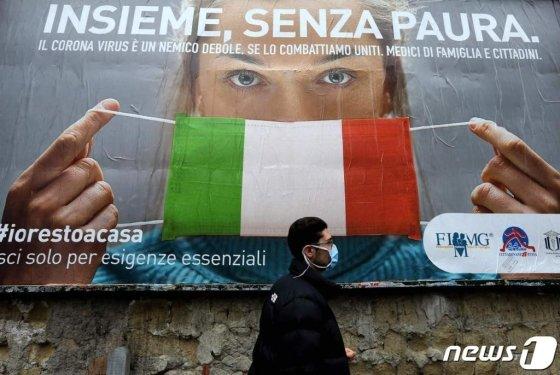 22일 이탈리아 나폴리 거리에서 한 남성이 코로나-19의 확산에 맞서기 위해 이탈리아 정부가 제작한 대형 광고판 앞을 지나가고 있다.  /사진제공=뉴스1