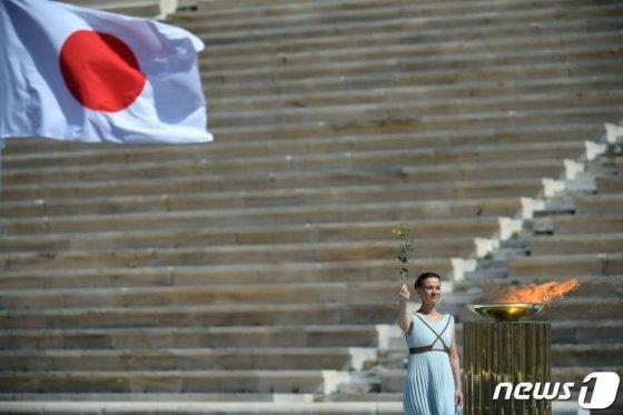 그리스 배우 산티 게오르기오가 19일 (현지시간) 아테네에서 열린 도쿄 올림픽 성화 인수식에서 성화를 들고 있다.  / 사진=AFP(뉴스1)