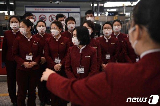 24일 (현지시간) 베이징 공항 체크인 구역에서 코로나 19의 감염을 예방하기 위해 에어 차이나 승무원들이 마스크를 쓰고 모여 있다. © AFP=뉴스1 © News1 우동명 기자