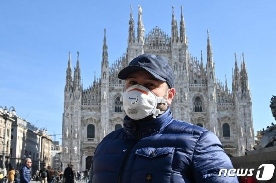 이탈리아 북부 밀라노에서 코로나19에 대한 우려로 마스크를 착용한 한 시민이 두오모 대성당 앞을 지나가고 있다./ AFP=뉴스1
