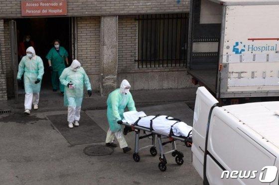 25일 (현지시간) 스페인 마드리드의 그레고리오 마라논 병원에서 의료진들이 숨진 코로나19 환자를 이송하고 있다. / 사진=AFP(뉴스1)