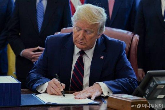 [워싱턴=AP/뉴시스]27일(현지시간) 도널드 트럼프 미국 대통령이 백악관 집무실에서 2조2000억 달러 규모의 신종 코로나바이러스 감염증(코로나19) 경기 부양 패키지 법안에 서명하고 있다. 2020.03.28.
