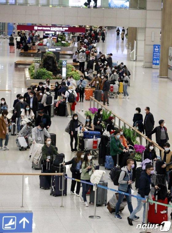 (인천공항=뉴스1) 권현진 기자 = 유럽에서 국내로 들어오는 모든 입국자 전원을 대상으로 신종 코로나바이러스 감염증(코로나19) 진단 검사를 시작한 22일 오후 유럽발 입국자들이 인천공항을 통해 귀국해 검사를 위해 길게 줄을 서 있다. 유럽발 입국자 중 유증상자는 검역소 격리시설에서, 무증상자는 지정된 임시생활시설에서 검사를 받는다. 2020.3.22/뉴스1