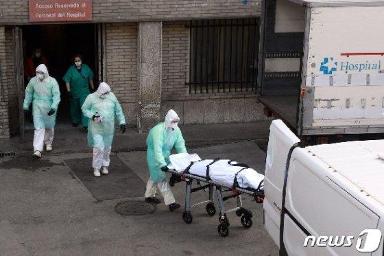 25일 (현지시간) 스페인 마드리드의 그레고리오 마라논 병원에서 의료진들이 숨진 코로나19 환자를 이송하고 있다. © AFP=뉴스1 © News1 우동명 기자