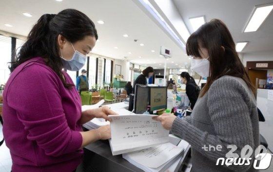 (서울=뉴스1) 이재명 기자 = 3월30일 오후 서울 송파구 마천2동 주민센터에서 한 시민이 선거인명부를 열람 하고 있다.  선거인명부에 누락 또는 잘못 표기돼 있거나 자격이 없는 선거인이 올라 있다고 확인되면, 열람 기간에 구두나 서면으로 이의를 신청할 수 있다. 2020.3.30/뉴스1