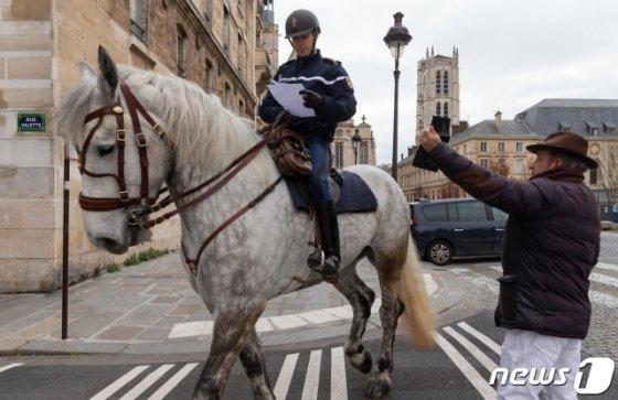 (파리(프랑스)=뉴스1) 이준성 프리랜서 기자 = 프랑스 정부가 전역에 이동제한령을 내린 후 첫 주말인 22일(현지시간) 오전 파리의 거리에서 기마경찰이 시민들의 통행증을 확인하고 있다.  신종 코로나바이러스 감염증(코로나19)의 추가 확산을 막기 위해 프랑스 정부는 지난 17일부터 약 15일 동안 전 국민을 상대로 의약품과 생필품 구입 등 필수적인 사유가 아니면 이동과 여행을 제한하고 있다. 2020.3.22/뉴스1