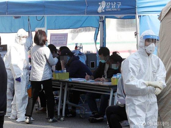 최근 귀국한 유학생을 중심으로 코로나19 확진자가 늘어나고 있는 가운데 지난달 30일 오후 서울 강남보건소에 마련된 선별진료소를 찾은 시민들이 문진표를 작성하고 있다./사진= 김창현 기자