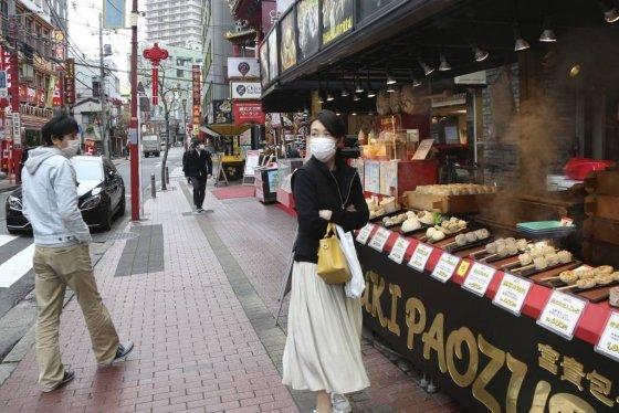 신종 코로나바이러스 감염증(코로나19) 확산을 막기 위해 마스크를 쓴 한 여성이 일본 도쿄 인근 요코하마의 차이나타운 상가에서 음식을 기다리고 있다. /사진=[요코하마=AP/뉴시스]
