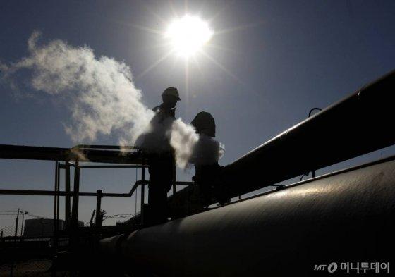 [브레가=AP/뉴시스] 2011년 리비아 브레가 항의 원유 파이프 주변을 직원들이 확인하는 모습.  2020.1.21.