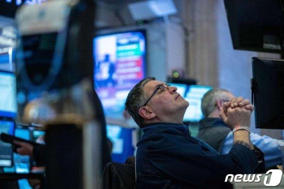 (뉴욕 AFP=뉴스1) 우동명 기자 = 11일(현지시간) WHO가 코로나19을 '팬데믹'으로 선언하면서 투자심리가 크게 위축돼 뉴욕증시가 또다시 폭락하자 트레이더가 전광판을 보며 기도하는 모습을 하고 있다.   ⓒ AFP=뉴스1