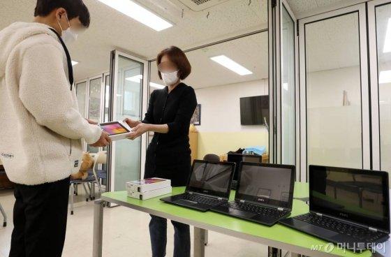온라인 개학을 하루 앞둔 8일 서울시내 한 중학교에서 교사가 학생에게 대여 스마트기기를 전달하고 있다./사진=김휘선 기자