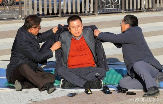 황교안 미래통합당 대표가 지난해 12월 20일 오후 청와대 분수대에서 총체적 국정실패 규탄을 위한 단식 투쟁에 들어간 뒤 김문수(왼쪽) 전 경기지사, 차명진 전 의원의 도움을 받아 점퍼를 입고 있다. /사진제공=뉴시스