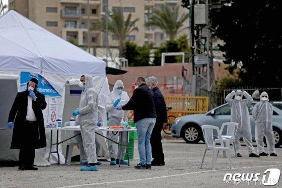 (예루살렘 AFP=뉴스1) 우동명 기자 = 2일 (현지시간) 코로나 19 감염증 확산 속 총선이 실시된 이스라엘 예루살렘의 특별 투표소에서 자가 격리 유권자들이 마스크를 쓰고 투표를 하고 있다.  ⓒ AFP=뉴스1