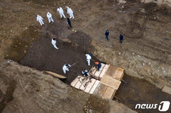 9일 (현지시간) 뉴욕의 하트 아일랜드에서 방호복을 입은 인부들이 코로나19 사망자의 관을 매장하고 있다. © 로이터=뉴스1 © News1 우동명 기자