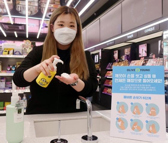 지난 12일 '올리브영 홍대' 매장을 방문한 고객이 30초 손 씻기 캠페인에 참여하고 있는 모습 /사진제공=올리브영