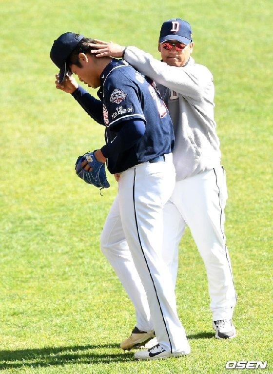 투구를 마친 뒤 김민재(오른쪽) 코치로부터 격려를 받는 이동원.
