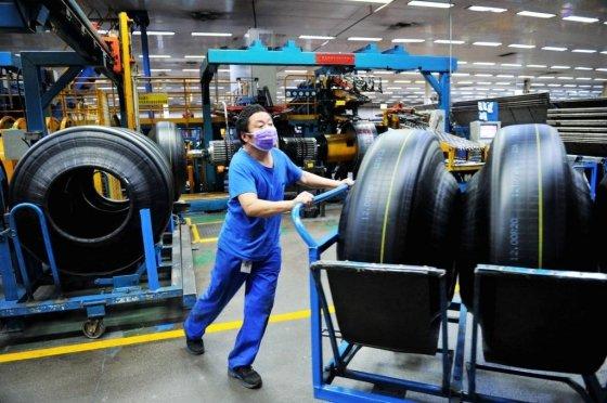 [칭다오=AP/뉴시스] 24일(현지시간) 중국 산둥성 칭다오시에 위치한 공장에서 마스크를 낀 노동자가 제조된 타이어를 옮기고 있다. 2020.02.28.