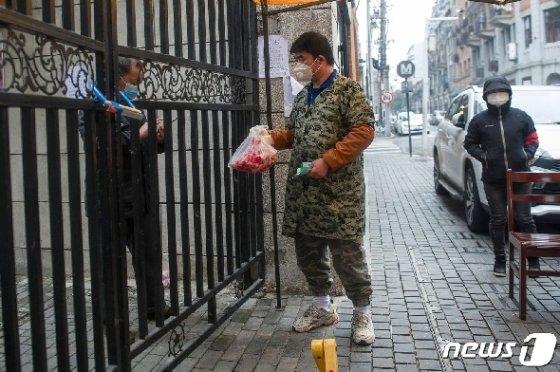 지난달 코로나 19 감염증 발원지인 후베이성 우한에서 마스크 쓴 행상인이 주민에게 음식을 배달하고 있다. © AFP=뉴스1 © News1 우동명 기자