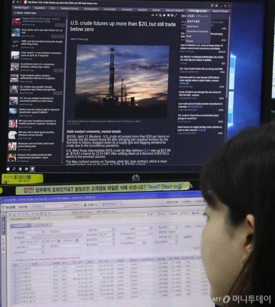 [서울=뉴시스] 전진환 기자 = 미국산 원유를 중심으로한 국제유가가 폭락한 21일 오전 서울 중구 하나은행 딜링룸에서 한 딜러가 유가 폭락 관련 기사를 열어놓고 업무를 보고 있다. 20일(현지시간) 뉴욕상업거래소(Nymex)에서 5월 인도분 서부텍사스산원유(WTI)는 배럴당 -37.63달러에 마감했다. 전 거래일 마감가(18.27달러) 대비 300% 넘게 폭락한 수치다. 2020.04.21.   amin2@newsis.com