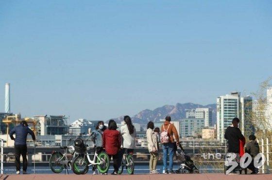 완연한 봄날씨를 보인 22일 서울 한강시민공원 여의도지구를 찾은 시민들이 구름 한 점 없는 하늘을 보며 오후 한때를 즐기고 있다.