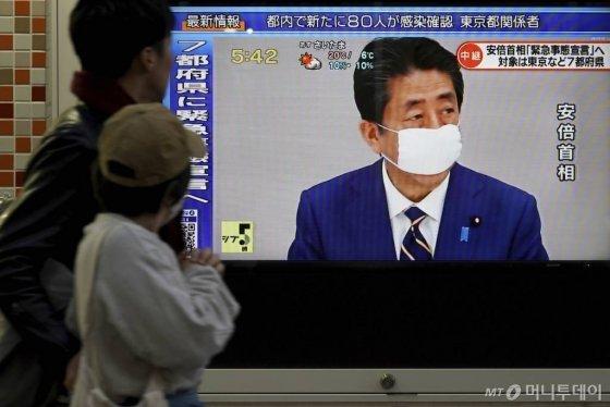 安倍晋三(安倍晋三)日本の首相が7日(火)東京で国家非常事態を宣言するの一歩行者がTVニュースを見るために停止している。 /写真= apニューシス
