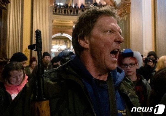 4월30일(현지시간) 코로나19 관련 봉쇄령 해제 등을 요구하며 미국 미시간주 의회 의사당에 진입한 무장 시위대 © 로이터=뉴스1