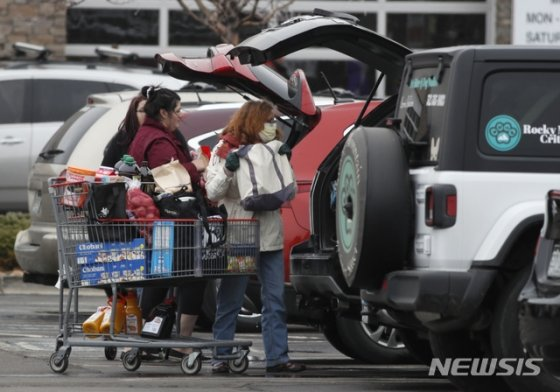 [손턴=AP/뉴시스]신종 코로나바이러스 감염증(코로나19)이 확산하는 가운데 2일(현지시간) 미국 콜로라도주 손턴의 코스트코 주차장에서 마스크를 낀 쇼핑객이 차에 물건을 담고 있다. 2020.04.16.