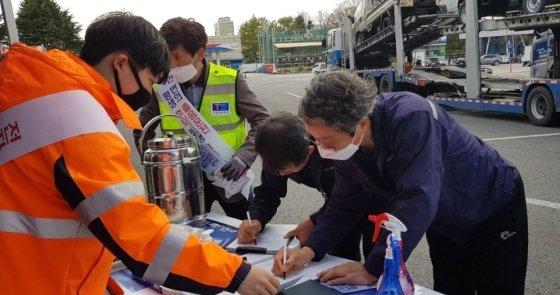 도로공사 직원이 고속도로 휴게소에서 화물차 운전자에게 '안전운전 실천 1만명 서약'을 받고 있다./사진=도로공사 제공