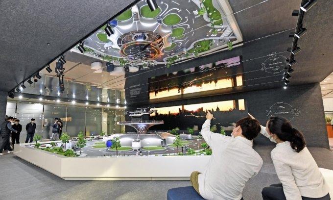 현대차 임직원들이 본사 1층 로비에 설치된 '스마트 모빌리티 솔루션' UAM, PBV, Hub의 축소 모형물을 관람하고 있다. /사진제공=현대차