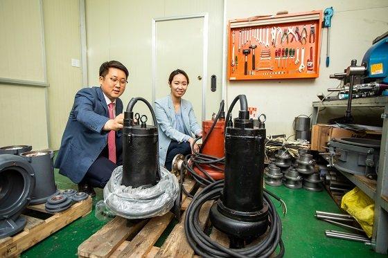 김진혁 박사(좌)와 차미영 황해전기 상무이사(우)가 개발된 단일채널 펌프를 바라보고 있다/사진=생기원