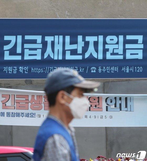 (서울=뉴스1) 허경 기자 = 전 국민이 받는 정부 긴급재난지원금 지급이 시작된 4일 서울 종로구의 한 주민센터에 긴급재난지원금 안내 현수막이 걸려 있다. 기초수급자 등 지원이 시급한 계층은 별도 신청 없이 이날 오후부터 기존 계좌를 통해 수령할 수 있으며, 그 외 가구도 지급 관련 정보를 조회할 수 있다.  행정안전부에 따르면 우선 지급대상자는 이날 오후 5시쯤부터 기존 복지전달체계에서 활용하던 계좌에서 긴급재난지원금 수령 여부를 확인할 수 있다. 2020.5.4/뉴스1