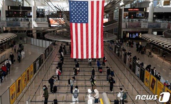 코로나19 팬데믹 상황 속 뉴욕 퀸즈의 JFK 공항 터미널에서 마스크 쓴 승객들이 거리를 두고 줄을 서 있다. / 사진=AFP(뉴스1)