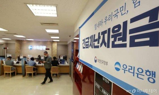 정부 긴급재난지원금 현장 신청 첫 날인 지난 18일 오전 서울 중구 우리은행 을지로지점에서 시민들이 상담을 받고 있다. / 사진=김휘선 기자 hwijpg@