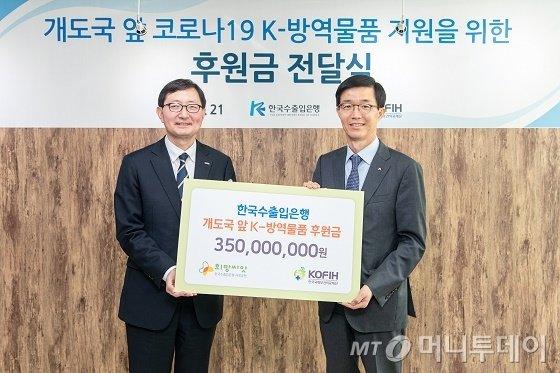 방문규 수출입은행장(오른쪽)은 21일 서울 중구 한국국제보건의료재단(KOFIH)에서 추무진 KOFIH 이사장에게 개발도상국에 한국산 방역물품 지원을 위한 후원금 3억5000만원을 전달했다./사진제공=수출입은행