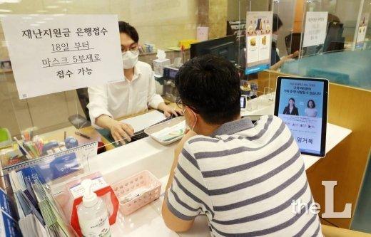 정부 긴급재난지원금 현장 신청 첫 날인 18일 오전 서울 중구 우리은행 을지로지점에서 시민들이 상담을 받고 있다.