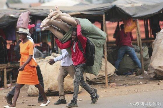 [하라레=AP/뉴시스]2일(현지시간) 짐바브웨 수도 하라레에서 한 남성이 마네킹 꾸러미를 어깨에 짊어지고 가고 있다. 2020.03.03.
